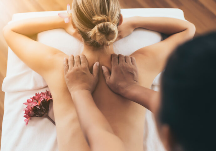 Traditional masseuse massaging on customers back at spa salon. Customer relieve from stressed. Caucasian woman get relax, calm.  Beautiful woman enjoying spa body massage on bed at spa salon room.